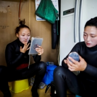 Jin So-hee and Woo Jung-min apply eco-friendly sun screen as they prepare to work in the sea off Geoje. | REUTERS