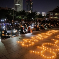 Participants including Myanmar residents in Japan and monks hold a candlelight vigil to protest against Myanmar's military coup and mourn protesters killed in the crackdown at Zojoji temple in Tokyo on Sunday. | REUTERS