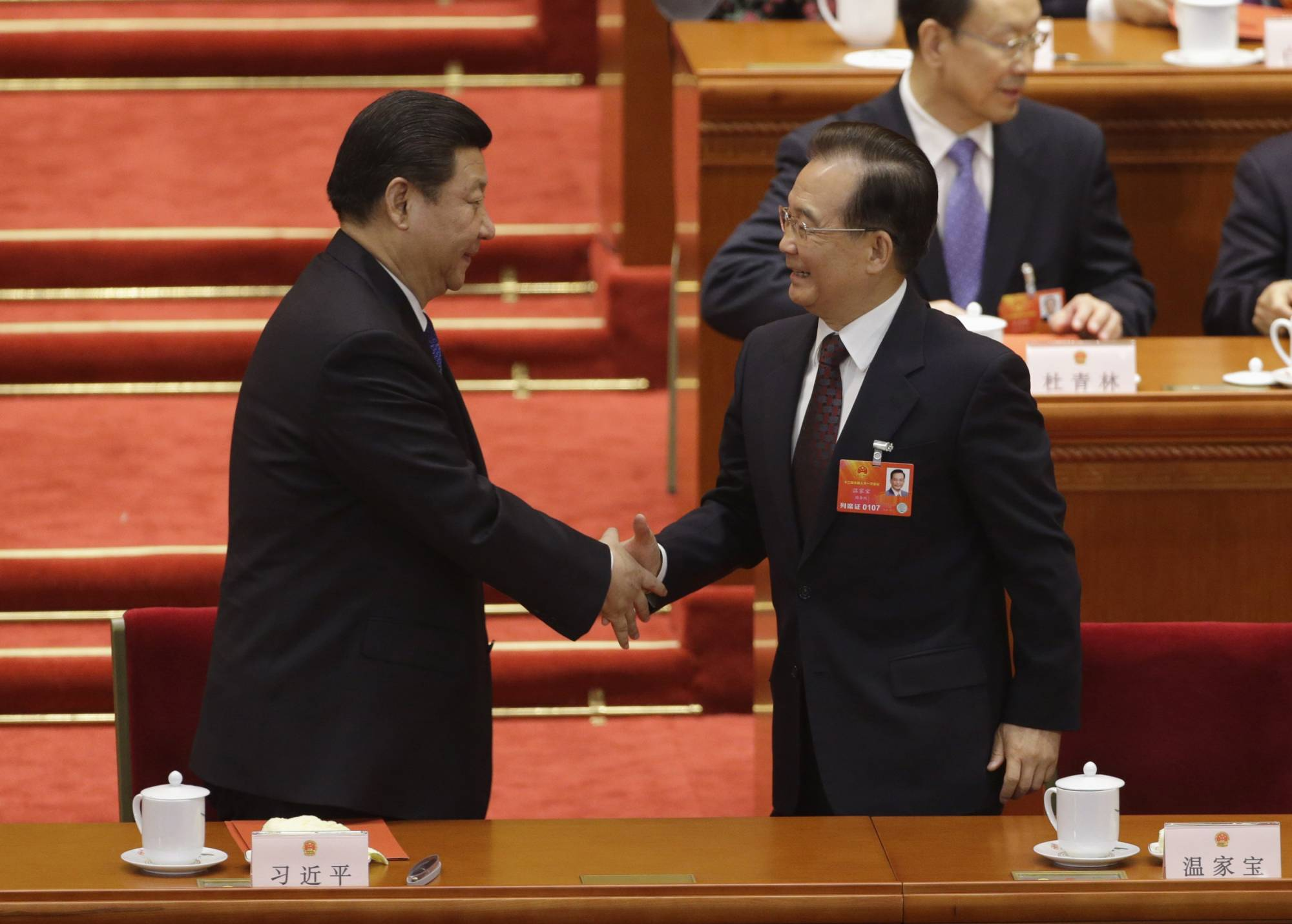 Newly elected Chinese President Xi Jinping and former Premier Wen Jiabao shake hands during a meeting of the National People's Congress at Beijing's Great Hall of the People in March 2013.  | REUTERS