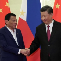 Philippine President Rodrigo Duterte shakes hands with Chinese leader Xi Jinping before a meeting at Beijing's Great Hall of People in April 2019.   | POOL / VIA REUTERS