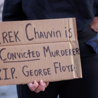 A woman holds a sign in New York following the guilty verdict in the trial over George Floyd's death. Standing at 1.93 meters, Floyd was known to friends and family as a 'gentle giant,' a rapper and athlete who suffered runs-in with the law and addiction but who wanted the best for his children. | REUTERS
