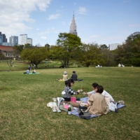 People enjoy a picnic at a park in Tokyo on April 3. | REUTERS