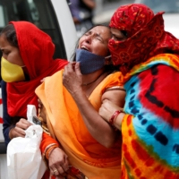 A woman is consoled after her husband died due to COVID-19 outside a hospital mortuary in Ahmedabad, India, on Tuesday.  | REUTERS