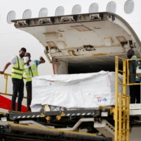 Workers offload boxes of AstraZeneca vaccines as Ghana receives its first batch of coronavirus shots under the COVAX scheme, at the international airport in Accra, in February. | REUTERS