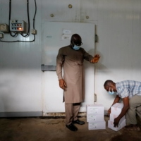 A worker prepares to store boxes of vaccines in a cold room in Accra, Ghana, in February.  | REUTERS