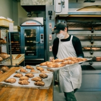 Staff take baked goods out of the oven at Bricolage Bread & Co. in Roppongi. | NATHALIE CANTACUZINO