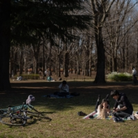 People picnic, relax and play outside in Tokyo's Yoyogi Park in March 2021. | RYUSEI TAKAHASHI