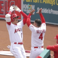 The Angels' Shohei Ohtani celebrates with teammate Jose Iglesias after hitting a home run against the Rangers during the third inning on Wednesday in Anaheim, California. | KYODO