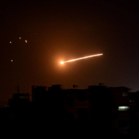 A streak of light is seen in the night sky in the vicinity of the Syrian capital Damascus during what Syrian authorities said was an Israeli air strike, in this handout released in February 2020. | SANA / VIA REUTERS