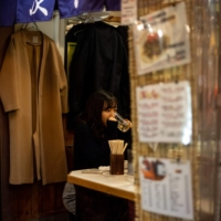 A diner drinks at a restaurant in Tokyo earlier this month. The serving of alcohol in restaurants and bars is likely to be banned under the latest state of emergency. | AFP-JIJI