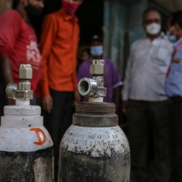 Workers load refilled oxygen tanks into a vehicle in Navi Mumbai, India, on Thursday. | BLOOMBERG