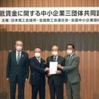 Akio Mimura (second from right), head of the Japan Chamber of Commerce and Industry, and others hold a news conference in Tokyo on April 15 to express their opposition to increasing the minimum wage. | KYODO