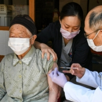 A doctor vaccinates a woman against COVID-19 in the village of Kitaaiki in Nagano Prefecture on Wednesday. | AFP-JIJI