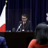 A viral gamble: Taro Kono, Japan's regulatory reform and vaccine minister, listens to a question from a journalist from behind a transparent screen during a news conference in February. Kono has pointed out that traveling during third and fourth waves of the pandemic may be riskier than waiting for your shot in Japan. | BLOOMBERG