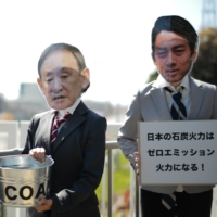 Protesters hold a rally Thursday in front of a coal-fired power plant in Yokosuka, Kanagawa Prefecture, while wearing masks portraying Prime Minister Yoshihide Suga and two ministers. | RYUSEI TAKAHASHI