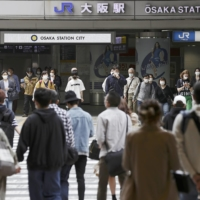 Pedestrians cross a street in front of JR Osaka Station on Saturday morning. | KYODO