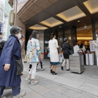 People visit a department store in Tokyo's Ginza district on Saturday. The government is requesting large commercial facilities, including department stores, to halt operationsa during the state of emergency set enter into effect Sunday.   | KYODO