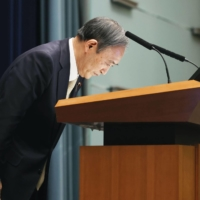 Prime Minister Yoshihide Suga bows during a news conference at the Prime Minister's Office on Friday as he calls for people's cooperation in containing the deadly coronavirus. | KYODO