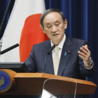 Prime Minister Yoshihide Suga speaks at a news conference at the Prime Minister's Office Friday after declaring a coronavirus state of emergency for four prefectures. | KYODO