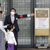 A department store employee in Tokyo's Ginza district guides customers at an entrance Sunday as the store was partially closed under the coronavirus state of emergency. | KYODO