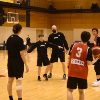 Japan women's basketball head coach Tom Hovasse (center) instructs his players during a provisional national team training camp in Tokyo on Thursday. | COURTESY OF JAPAN BASKETBALL ASSOCIATION