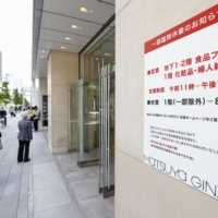 A sign at a department store in Tokyo's Ginza shopping district Sunday notes that the store is partially closed. | KYODO