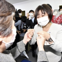 Haruko Miyaguchi (right), a former broadcaster backed by three opposition parties, bumps fists with a supporter after winning a seat in the Upper House in a by-election Sunday in Hiroshima. | KYODO