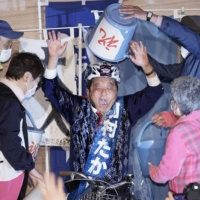 Nagoya Mayor Takashi Kawamura is doused in water by supporters after winning a fifth term in Sunday's election.  | KYODO
