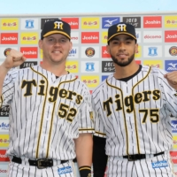Tigers outfielder Jerry Sands (left) and pitcher Robert Suarez celebrate after a win over the BayStars at Koshien Stadium in Nishinomiya, Hyogo Prefecture, on Sunday. | KYODO