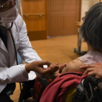 A doctor administers a dose of a COVID-19 vaccine at a nursing home in Kawasaki on April 12. | BLOOMBERG