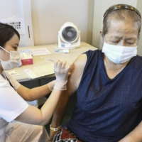 An elderly woman gets vaccinated in Okinawa Prefecture. | POOL / VIA KYODO