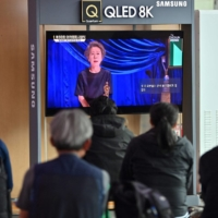 People watch a television screen at a train station in Seoul broadcasting live footage of South Korea's first Oscar-winning actress Youn Yuh-jung speaking at the 93rd Academy Awards ceremony. | AFP-JIJI