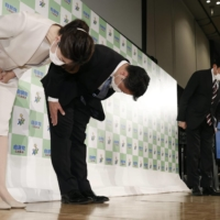 LDP Hiroshima chapter chair and former Foreign Minister Fumio Kishida (right) bows to supporters with LDP candidate Hidenori Nishita (center) after the latter lost an Upper House by-election in Hiroshima on Sunday. | KYODO