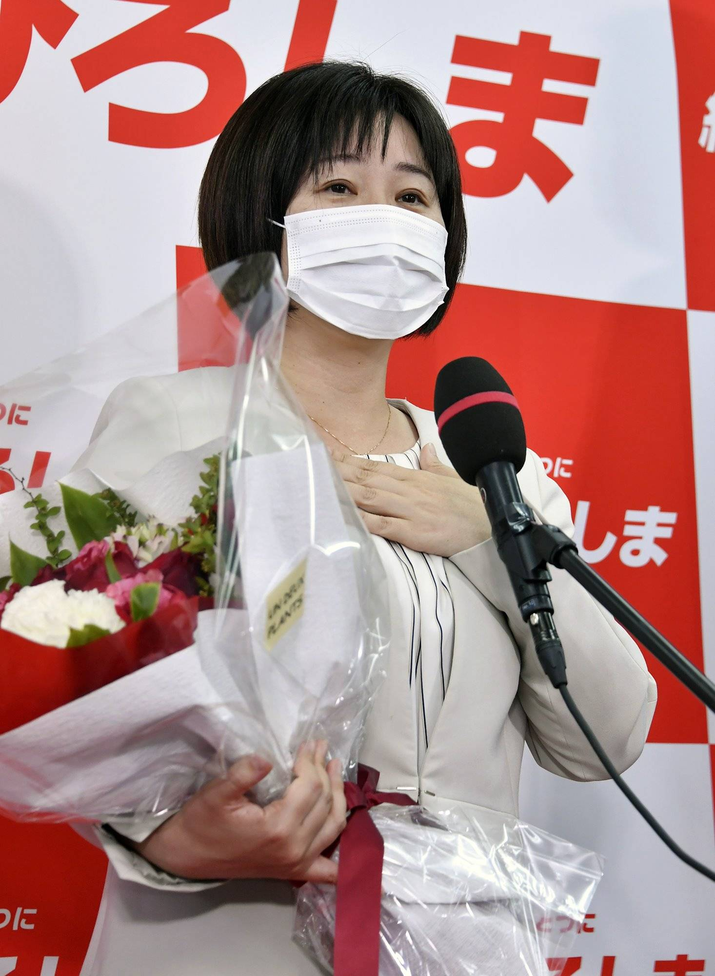 Haruko Miyaguchi, a former broadcaster backed by three opposition parties, speaks to supporters after winning a seat in the Upper House in a by-election Sunday in Hiroshima. | KYODO
