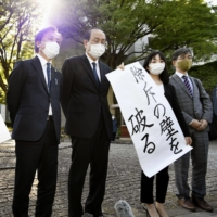 A plaintiff and his lawyers with banners saying victory outside the Supreme Court in Tokyo on Monday | KYODO