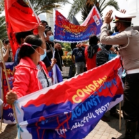 Police confront activists during a protest to support the anti-coup movement and democracy in Myanmar, near the Association of Southeast Asian Nations secretariat building in Jakarta on Saturday.  | REUTERS