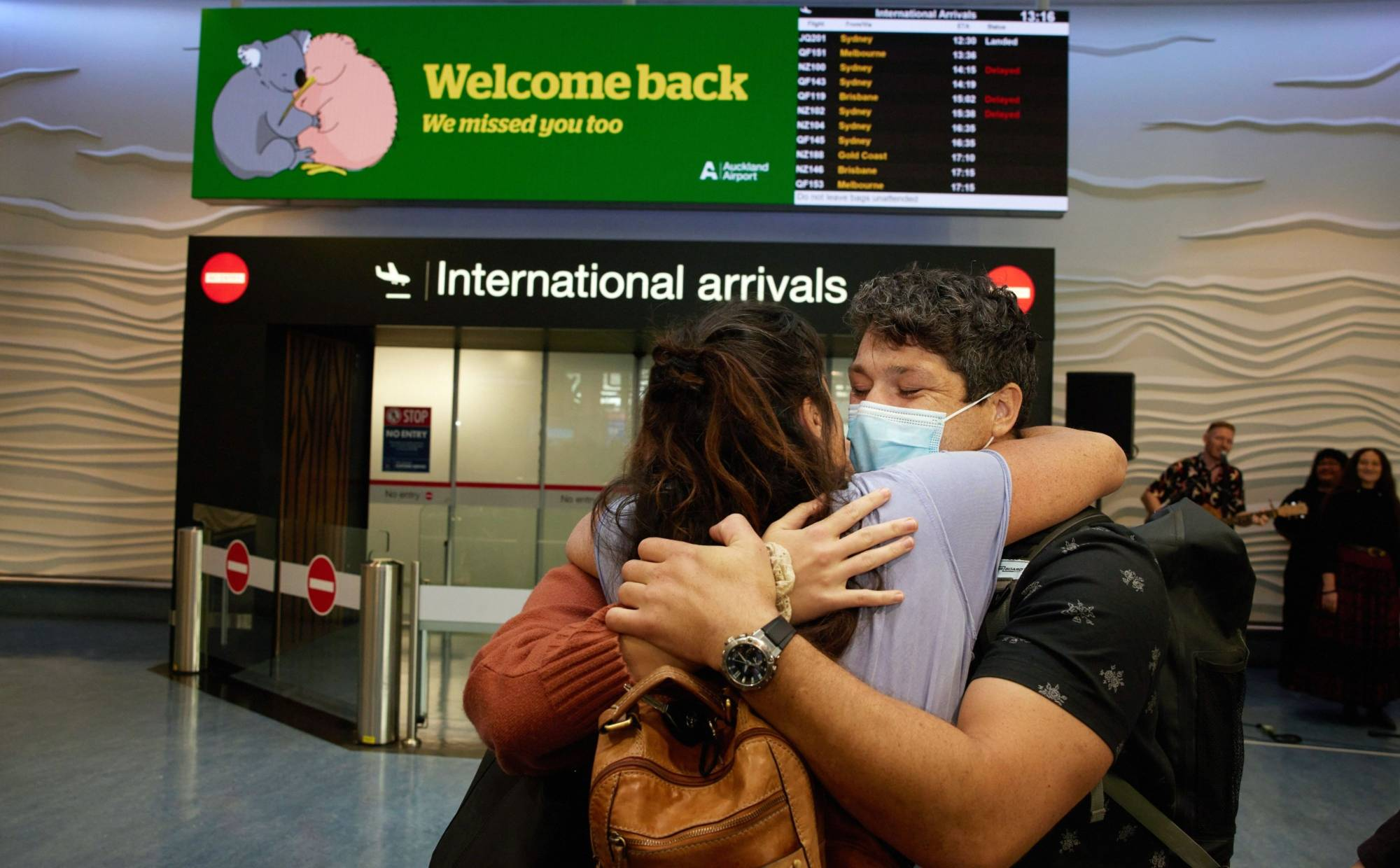 People embrace as they are reunited at Auckland International Airport on April 19.  | BLOOMBERG