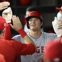 Angels starting pitcher Shohei Ohtani celebrates with teammates in the dugout after scoring against the Rangers in the sixth inning on Monday in Arlington, Texas. | USA TODAY / VIA REUTERS