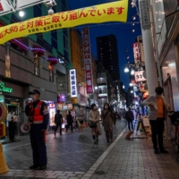 A security guard stands in an entertainment district in Tokyo calling for people to stay home after the capital was put under a fresh state of emergency. | AFP-JIJI