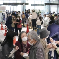 Older people visit the Kochi City Office to get reservations for vaccinations. | KYODO