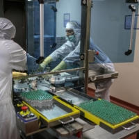 Employees work on the production of line for Covishield, the local name for the COVID-19 vaccine developed by AstraZeneca PLC and the University of Oxford, at the Serum Institute of India Ltd. Hadaspar plant in Pune, Maharashtra, India, in January.  | BLOOMBERG