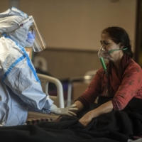 A health care worker speaks to a COVID-19 patient at a temporary treatment site set up near a hospital in Delhi on Friday.  | ATUL LOKE / THE NEW YORK TIMES