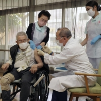 A doctor administers a COVID-19 vaccine at a nursing care facility in Kyoto on April 12. | POOL / VIA KYODO