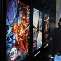 Movie goers line up next to an advertisement for 'Demon Slayer: Kimetsu no Yaiba the Movie: Mugen Train' outside a cinema in Tokyo in October. | BLOOMBERG
