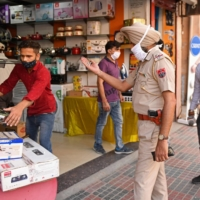 Police urge shopkeepers to close before a night curfew begins following the state government's directive to curb the spread of COVID-19 in Amritsar, India, on Tuesday. | AFP-JIJI