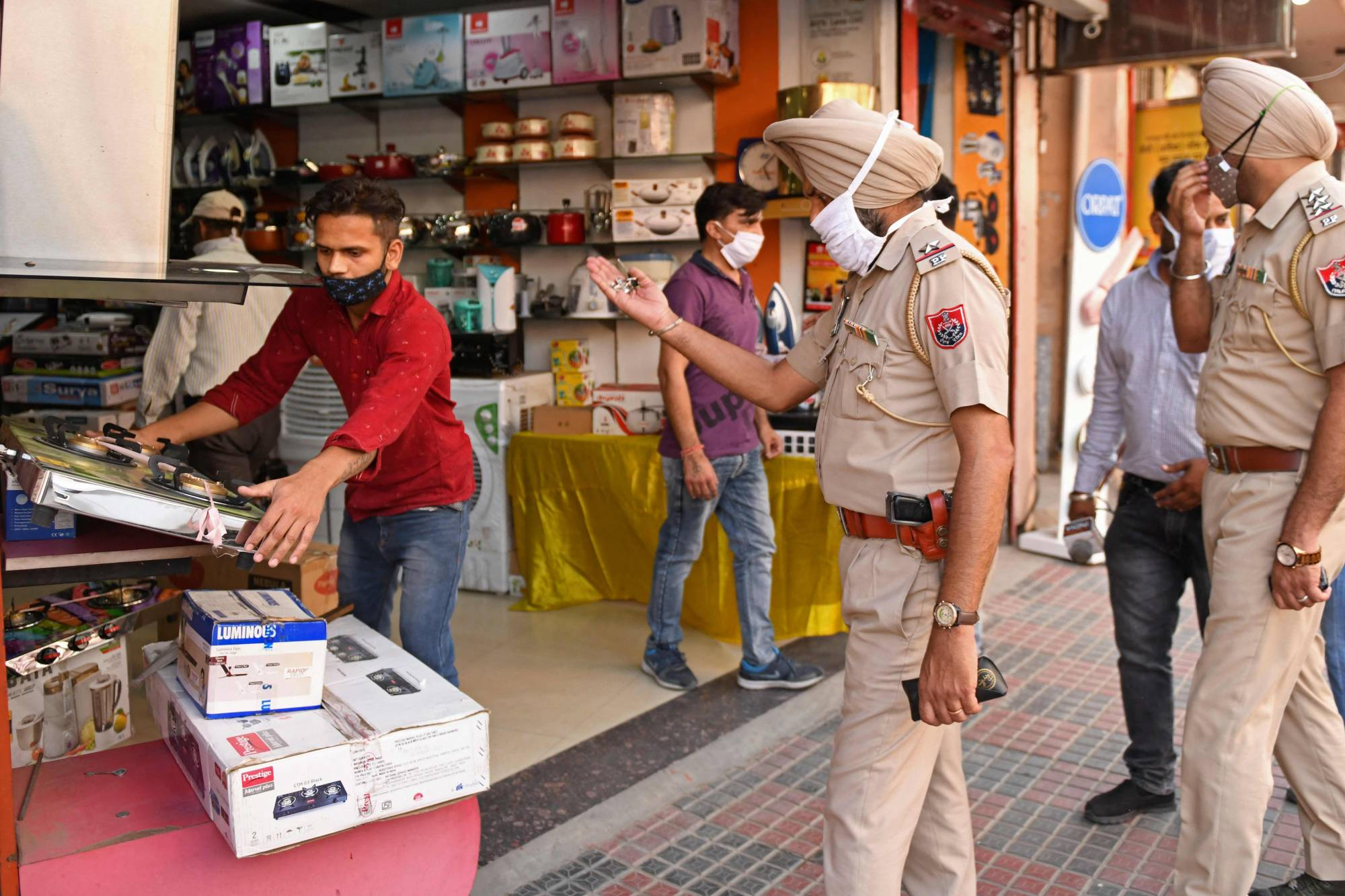 Police are urging traders to close before a nighttime curfew begins following the state government's directive to curb the spread of COVID-19 in Amritsar, India on Tuesday.  |  AFP-JIJI