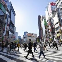 People walk in Tokyo's Shinjuku district on Monday. | KYODO