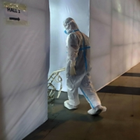 A health worker wheels an oxygen cylinder cart in a COVID-19 hospital set up inside a stadium in New Delhi on Friday.    BLOOMBERG
