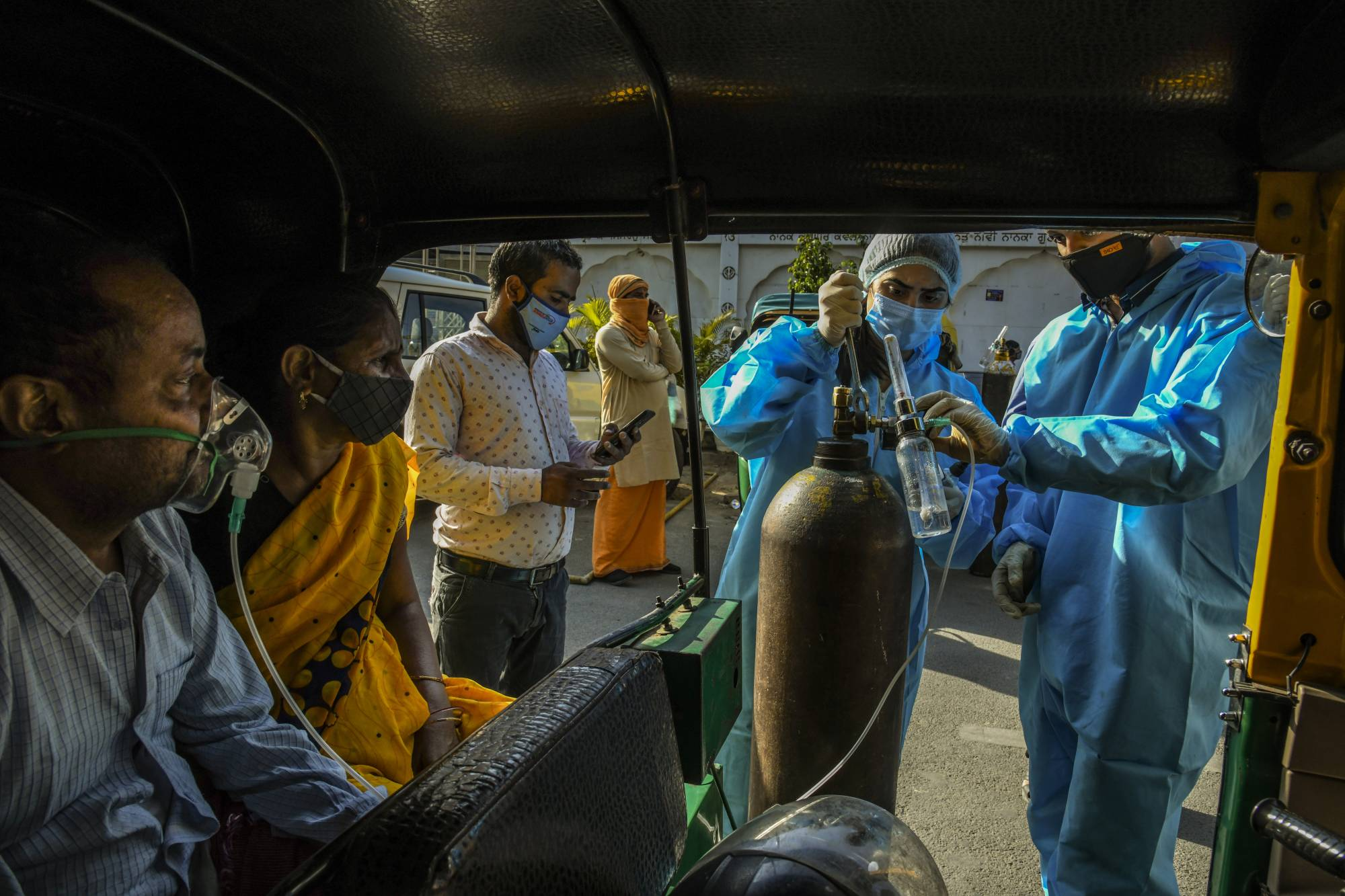 Coronavirus patients sitting in a rickshaw receive oxygen outside a Sikh house of worship in New Delhi on Sunday.  | ATUL LOKE / THE NEW YORK TIMES
