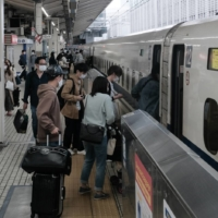 Passengers board an East Japan Railway Co. bullet train at Tokyo Station on Thursday.  | BLOOMBERG